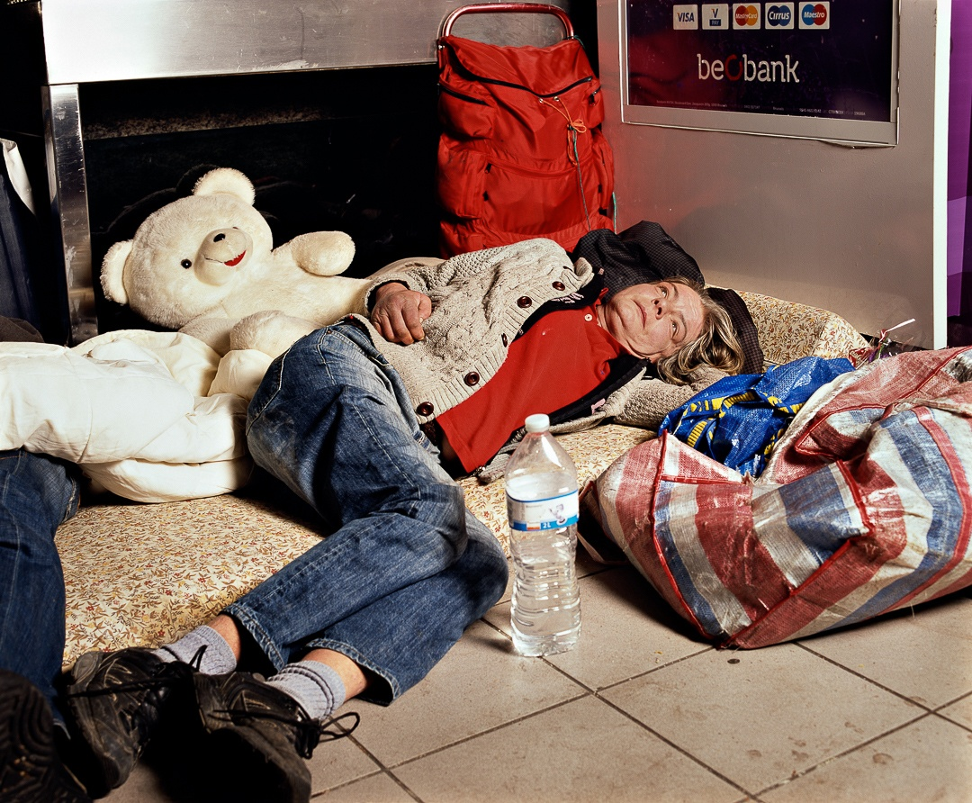 A photo of a homeless woman laying on cushions. She has blonde hair and is wearing jeans and a beige sweater. A white teddy bear is behind her.